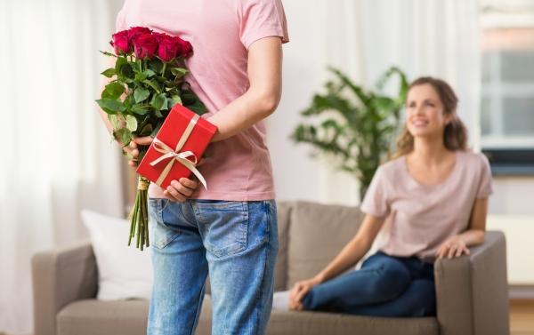 Mann versteckt Blumen und Geschenk hinter seinem Ruecken