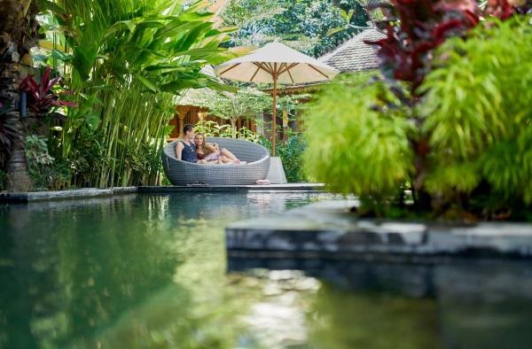 Ein junges Paar sitzt auf einem großen Sitzmöbel unter einem Sonnenschirm an einem paradisischen Pool
