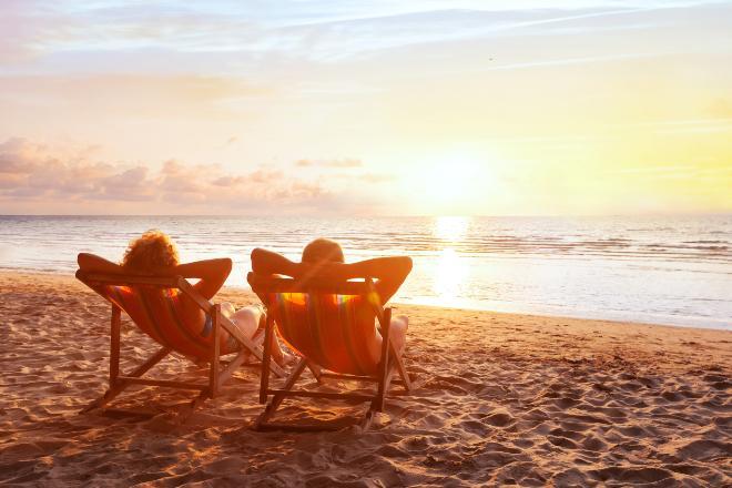 Paar liegt am Strand in Liegestühlen - Gemütliche Terrassenliegen als Alternative für zuhause