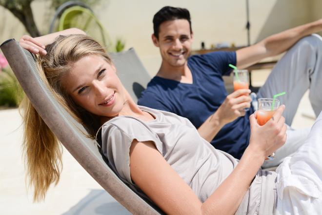 Junges Paar mit Getränken entspannt auf Terassenliegen